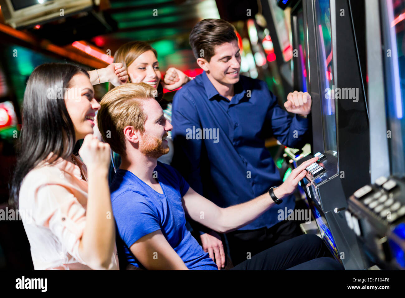 Young group of people gambling in a casino playing slot and various machines - Stock Image