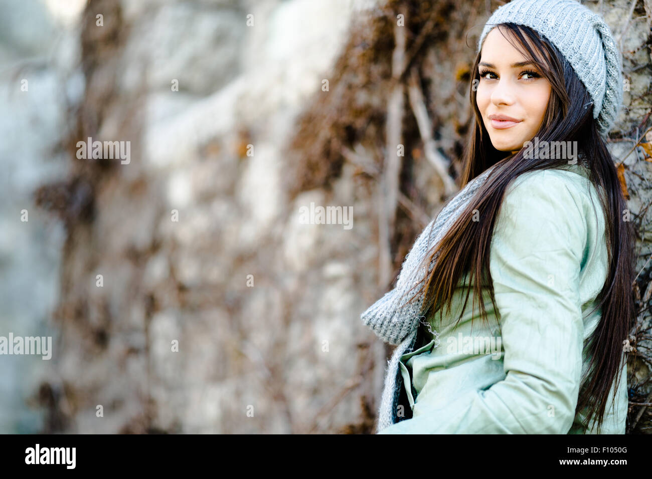 Portrait of a young beautiful woman in autumn ambient as leaning against a wall - Stock Image