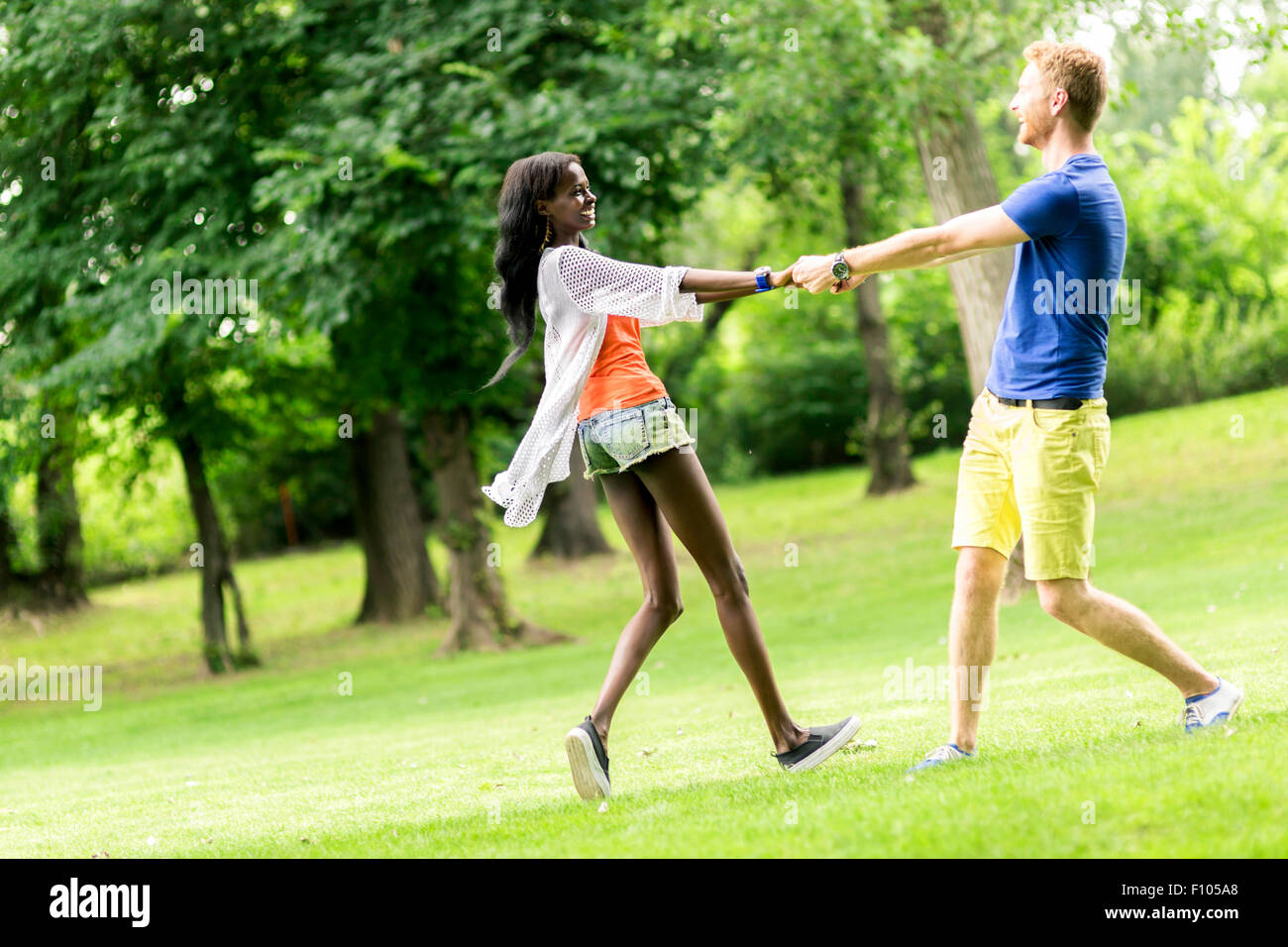 Beautiful couple dancing outdoors in a park displaying joy and love - Stock Image