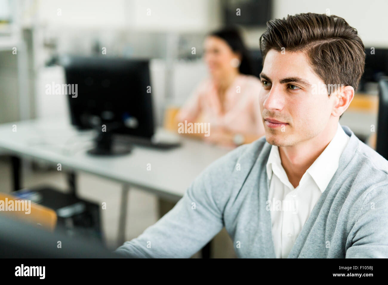Young handsome man studying information technology in a classroom - Stock Image