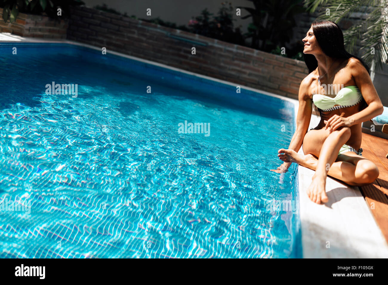 Young beautiful woman on the side of the pool playing with water displaying sensuality Stock Photo