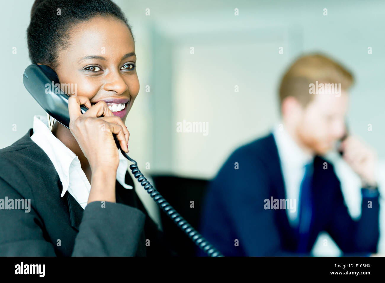 A beautiful, black, young woman working at a call center in an office with her red haird partner on the other end Stock Photo