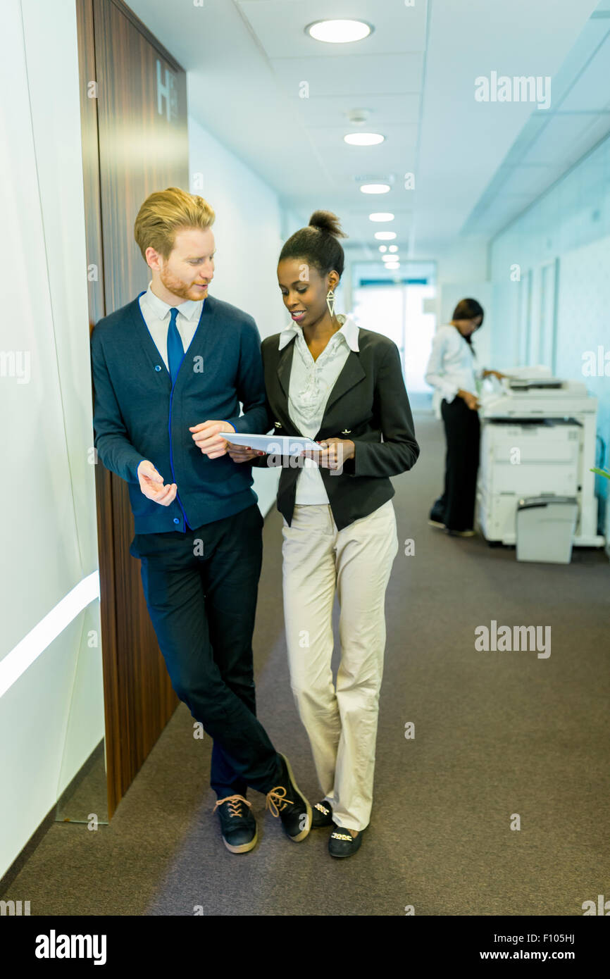 Two young business people discussing ideas on an office corridor while holding a tablet - Stock Image