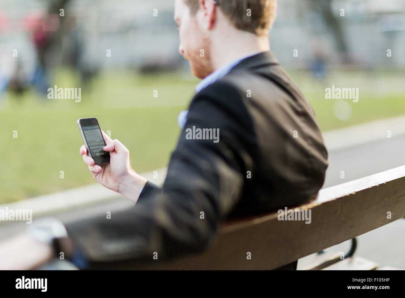 Businessman holding his cell phone while sitting on a park bench - Stock Image