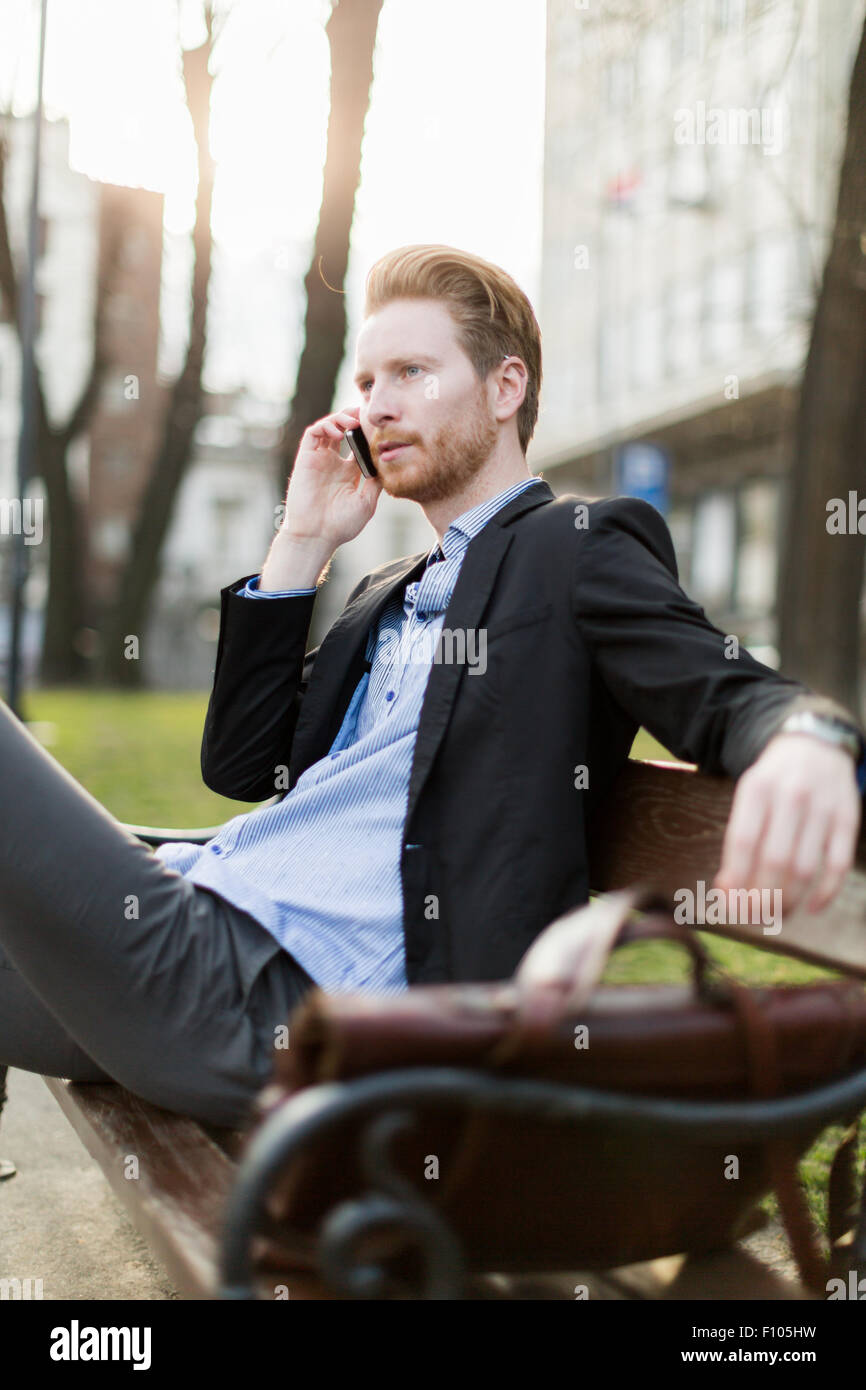 Businessman sitting on a  bench  and talking on the phone in nice sunshine - Stock Image
