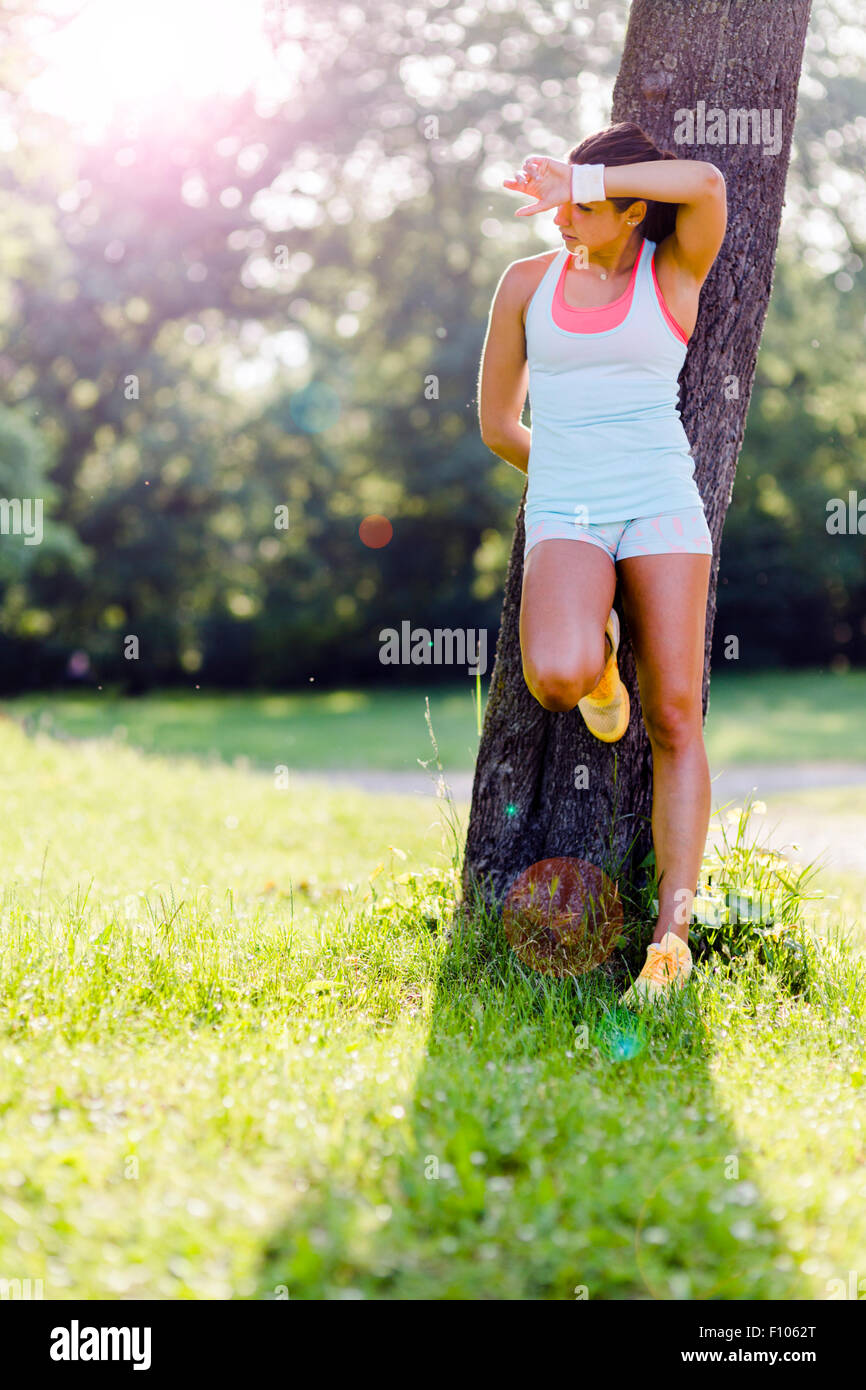 Young woman being exhausted after exercising in nature - Stock Image