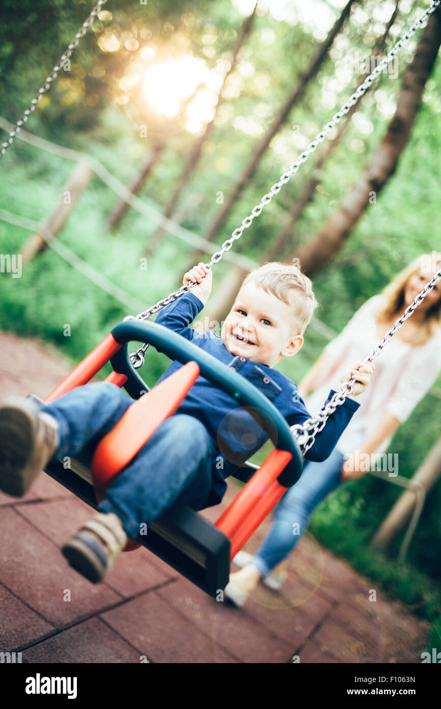 Mother and child outdoors in playground riding a  swing and smiling - Stock Image