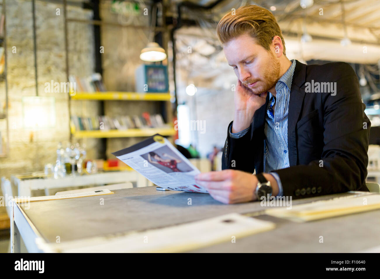 Confused businessman reading the paper in a restaurant - Stock Image