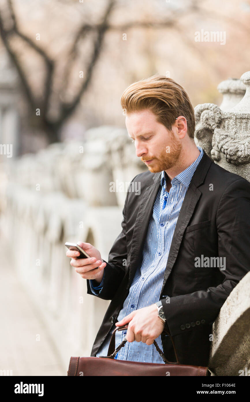 Businessman checking cell phone while holding a   bag - Stock Image