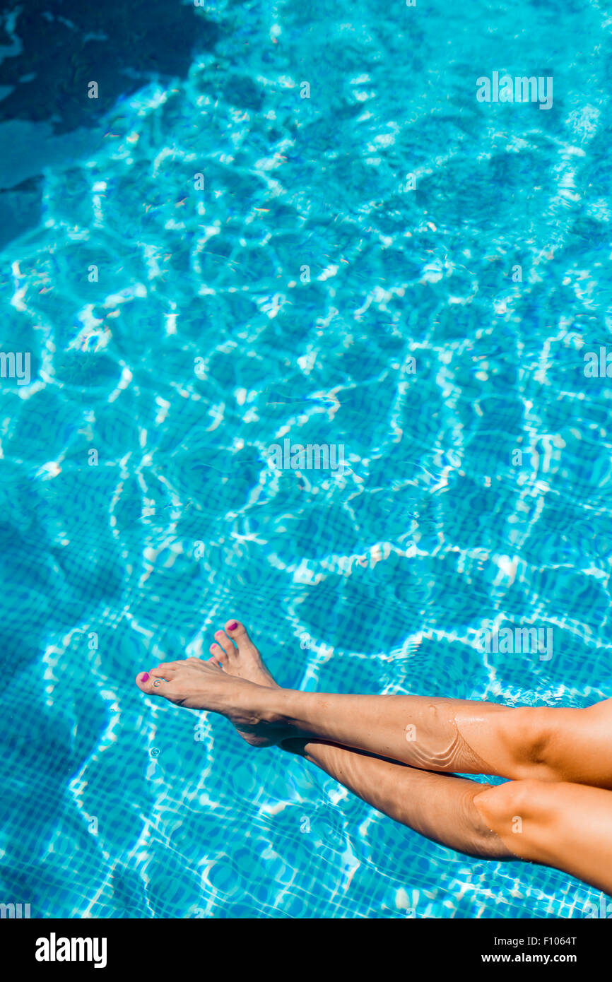Closeup of beautiful female legs in water of a pool - Stock Image