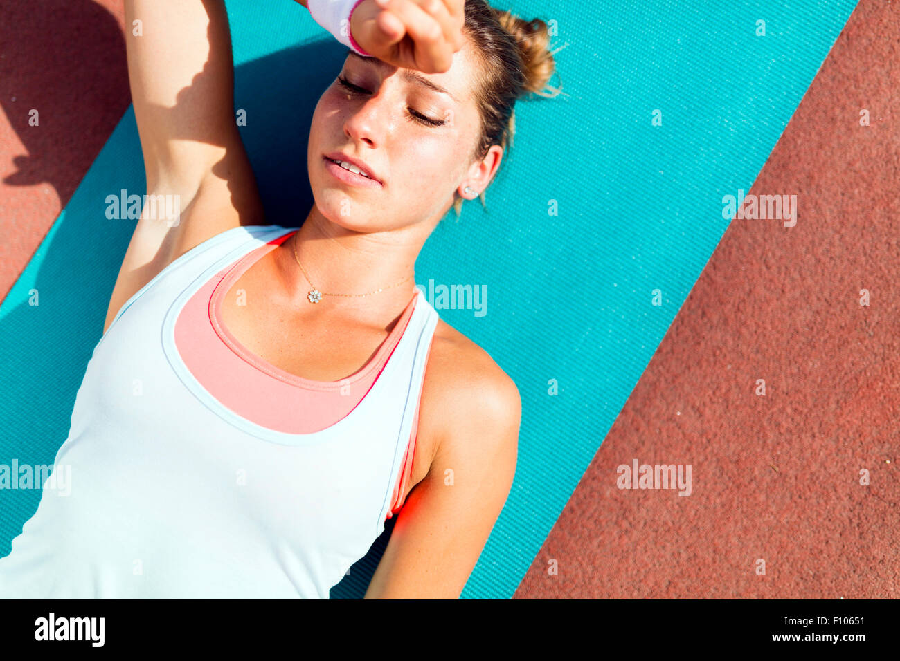 Exhausted beautiful young woman lying on a mat after exercise - Stock Image