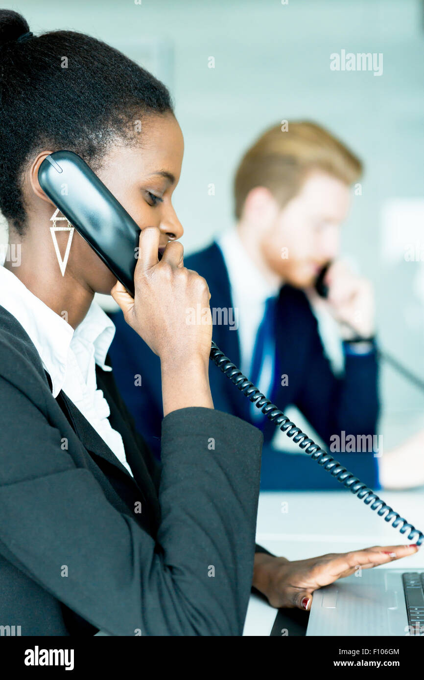 A beautiful, black, young woman working at a call center in an office with her red haird partner on the other end - Stock Image