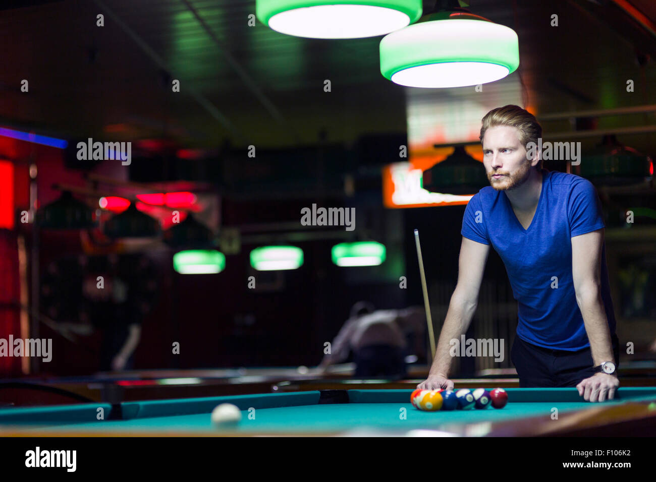 Handsome young snooker player bending over the table in a bar with beautiful ambient lighting - Stock Image