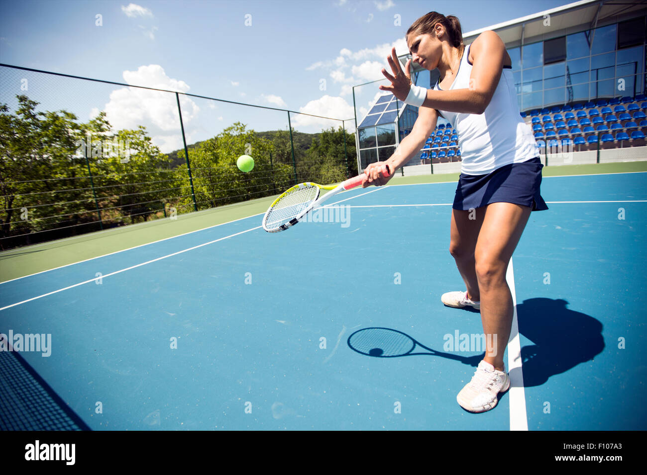 Female tennis player performing a drop shot on a nice blue court - Stock Image