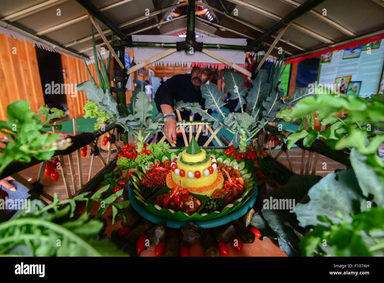 Elder of traditional Sundanese community prepares food offering for ceremony. - Stock Image
