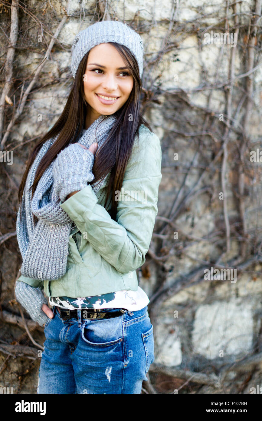 Portrait of a smiling  young woman wearing a scarf and a hat - Stock Image