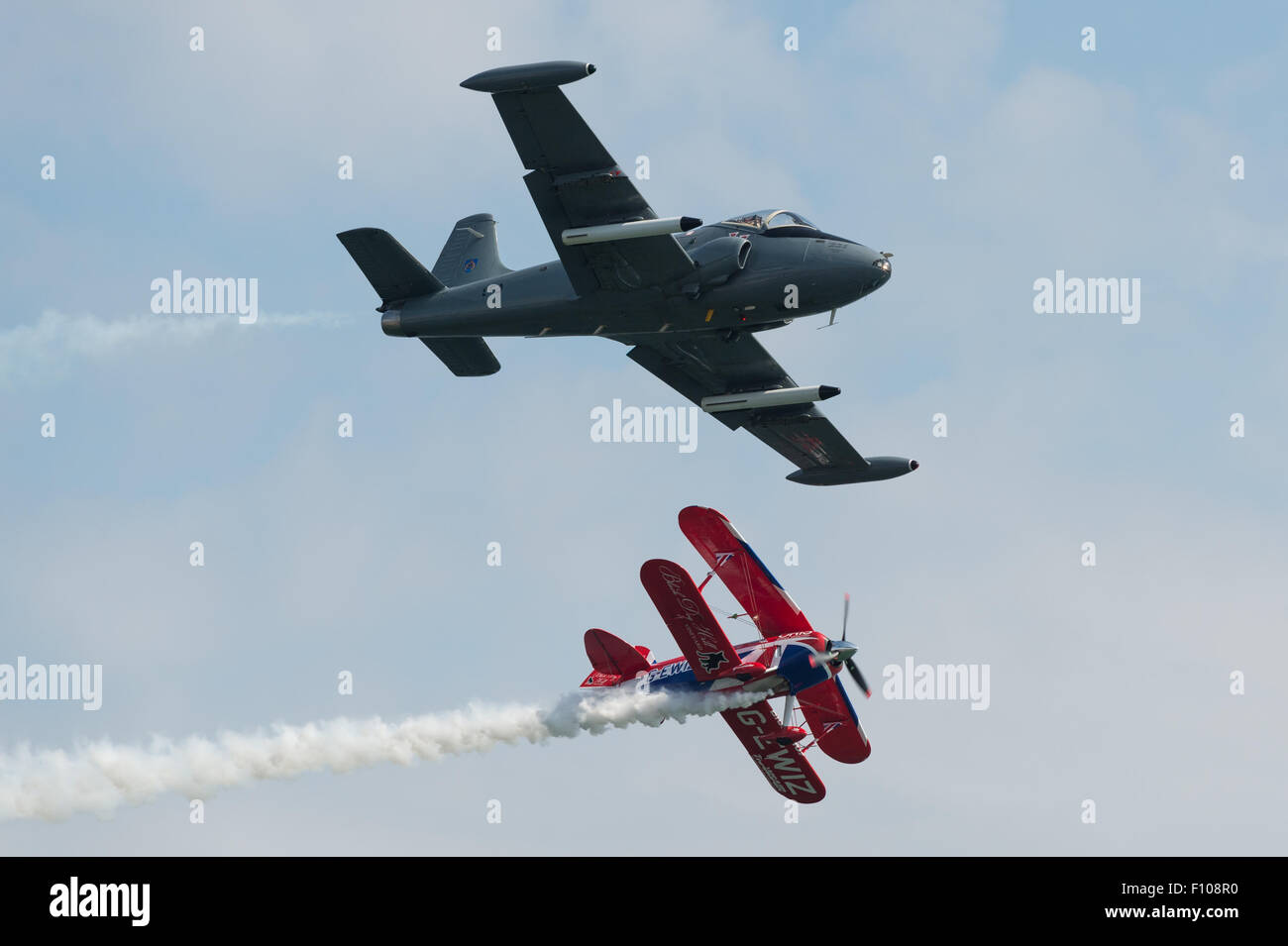 BAC Strikemaster jet trainer and Rich Goodwin's Muscle Pitts Biplane fly together at the Dawlish Air Show 2015. - Stock Image