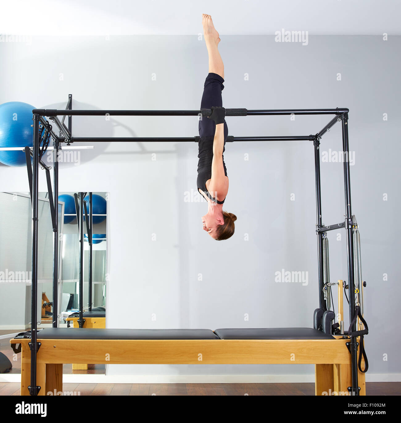 Cadillac Pilates: Pilates Woman In Cadillac Acrobatic Upside Down Balance Reformer Stock Photo: 86673628