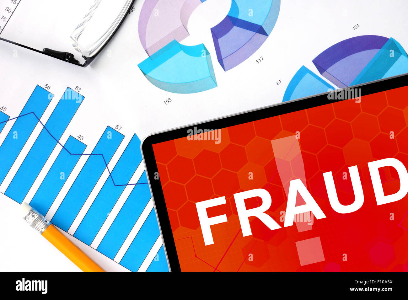 Tablet with word  fraud  and graphs. Concept photo. - Stock Image