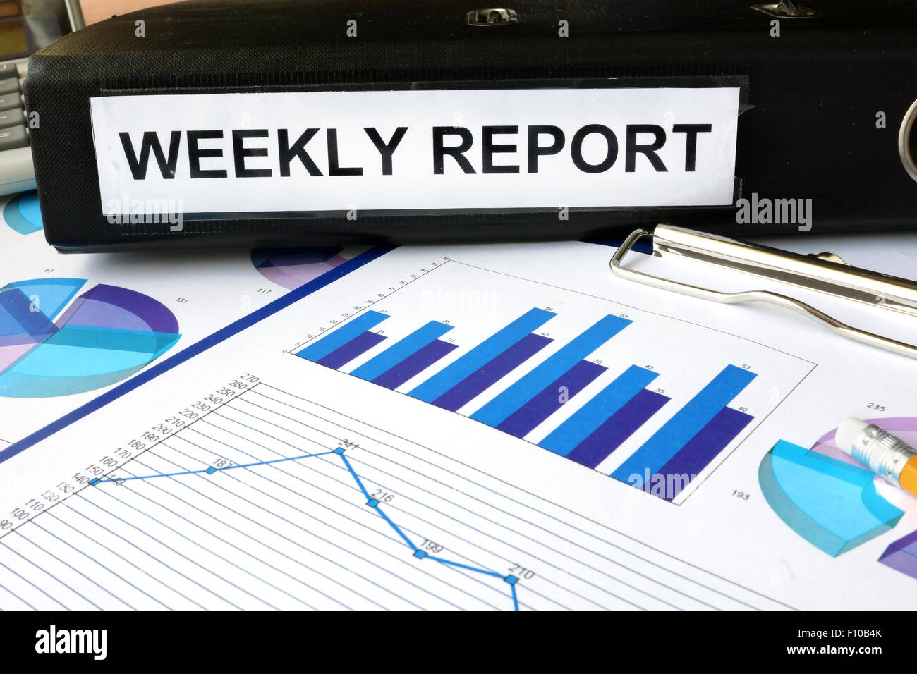 Folder with the label weekly report  and charts. - Stock Image