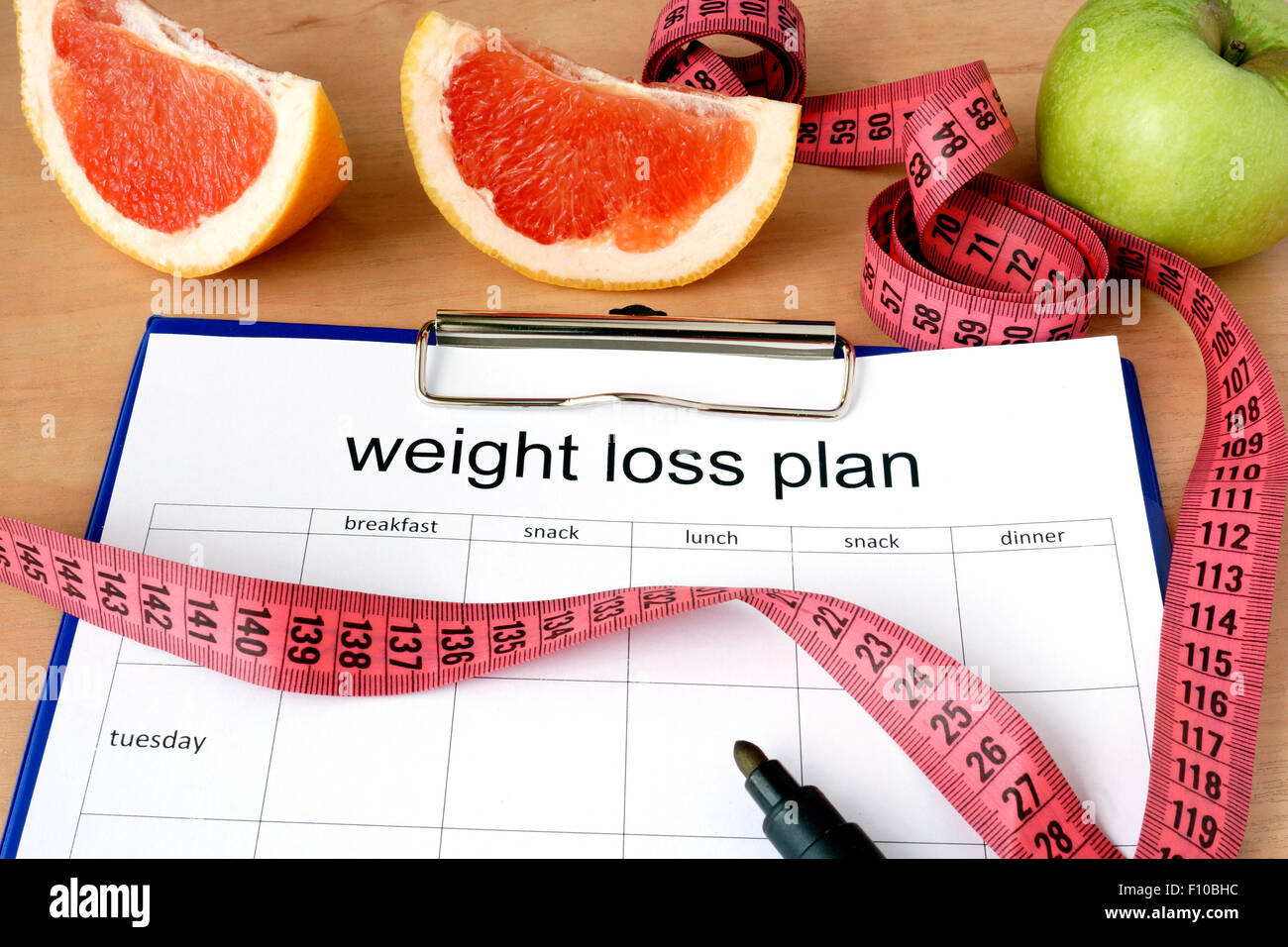 Paper with weight loss plan and grapefruit - Stock Image