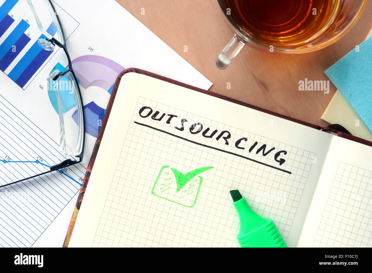 Notepad with word outsourcing concept and glasses - Stock Image