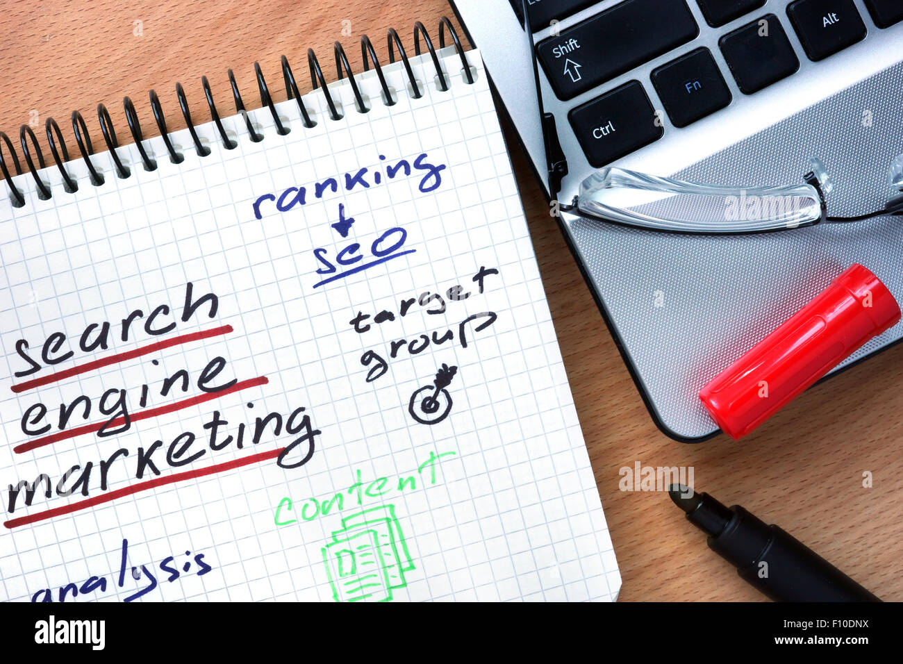 Notepad with words search engine marketing on a wooden background - Stock Image