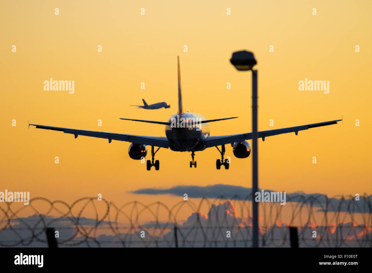 A British Airways Airbus A319 lands on Heathrow Airport's runway 27R as in the distance a British Airways A380 - Stock Image