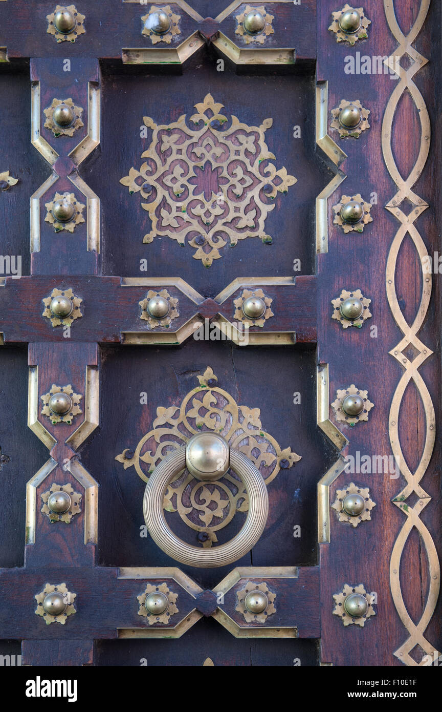 Jaipur, India. Panelled door with brass studs and decorations, and a large ring handle; City Palace - Stock Image