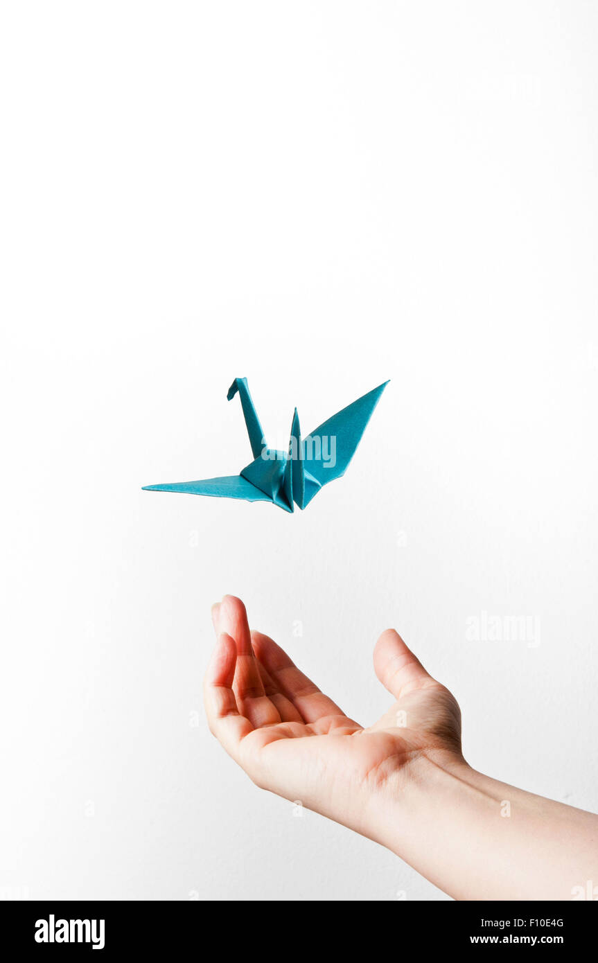 open female hand and origami bird flying away, imagination and creativity concept - Stock Image
