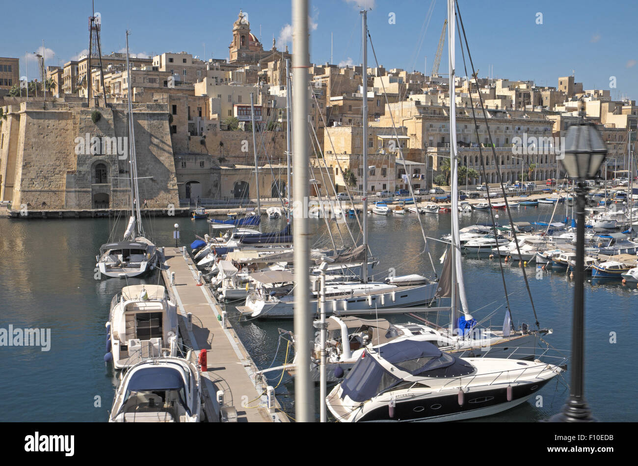 Yachts with old stone buildings and fortifications beyond, near Valletta, Malta. - Stock Image