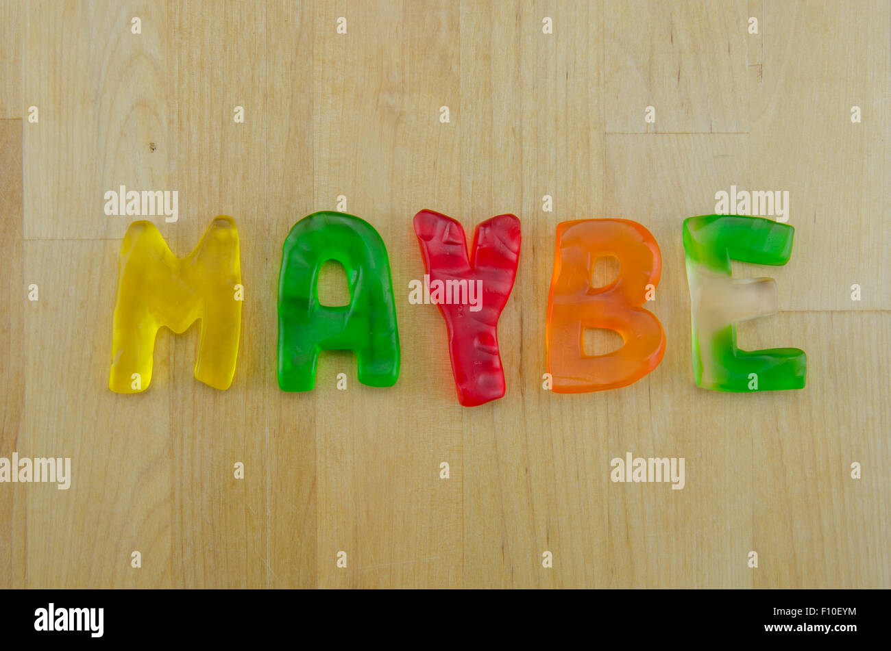 Multi colored gummy letters spell the word maybe - Stock Image