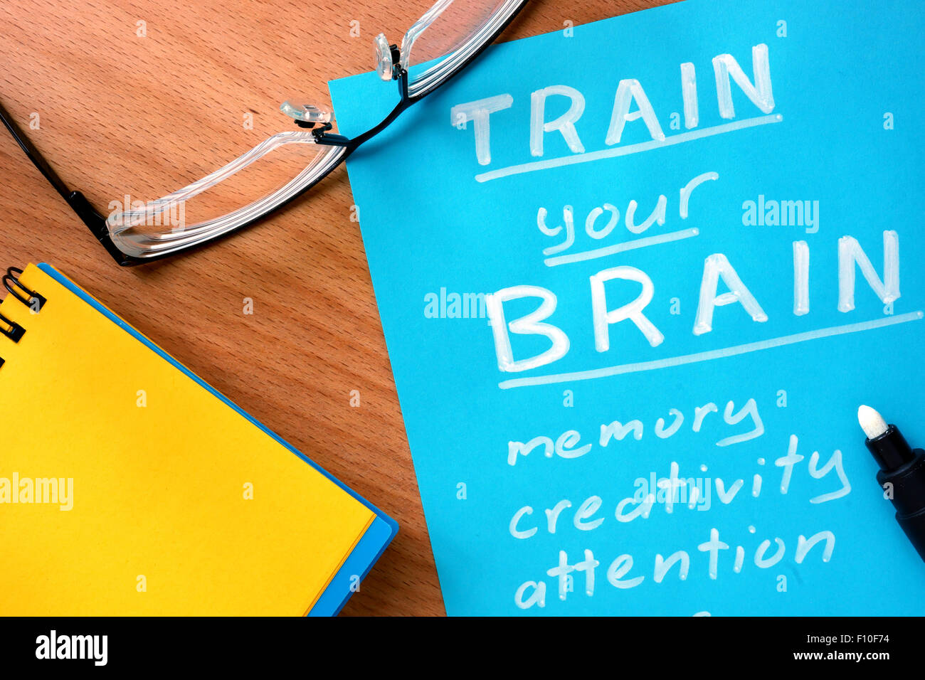 Blue paper with words Train your Brain and glasses. - Stock Image