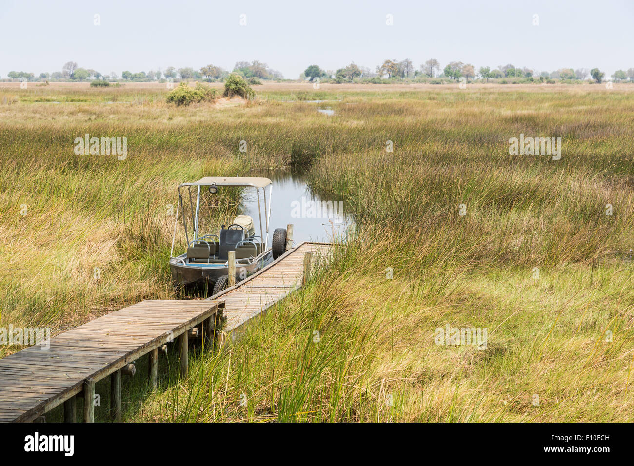 Safari motor boat moored at jetty in readiness for a river trip for sightseeing, Duba Plains camp, Okavango Delta, - Stock Image