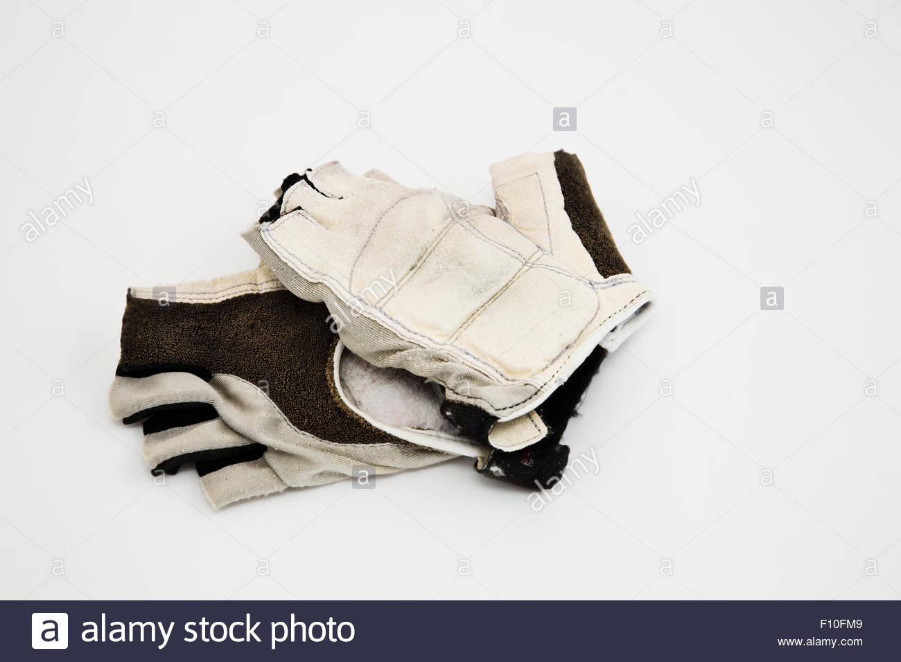 Worn out padded cycling gloves isolated on white with copy space - Stock Image