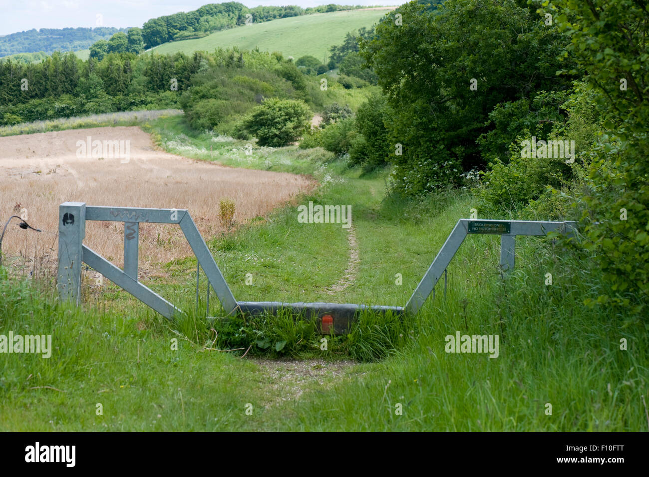 A metal vehicle barrier gate with a low centre section for riders on a bridleway on the Wessex Downs near West Woodhay, - Stock Image