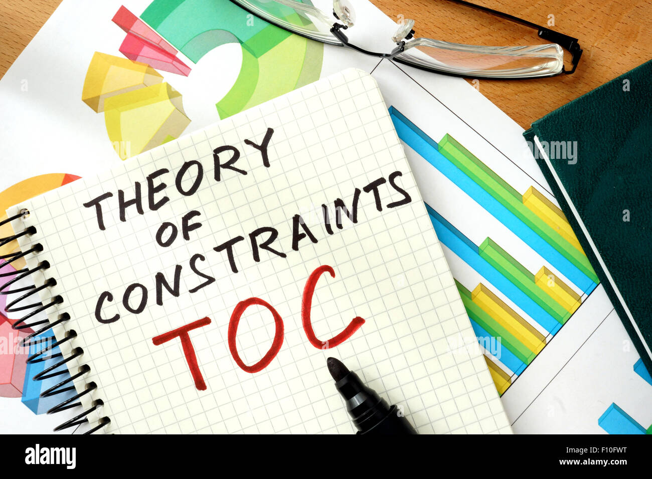 Words Theory of Constraints  TOC   on the notepad and charts. - Stock Image