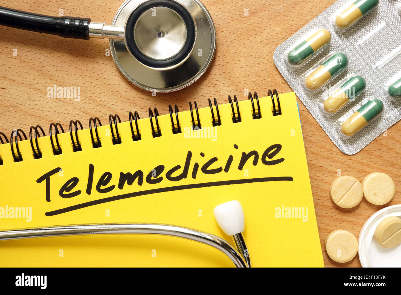 Notepad with telemedicine on a wooden table. - Stock Image