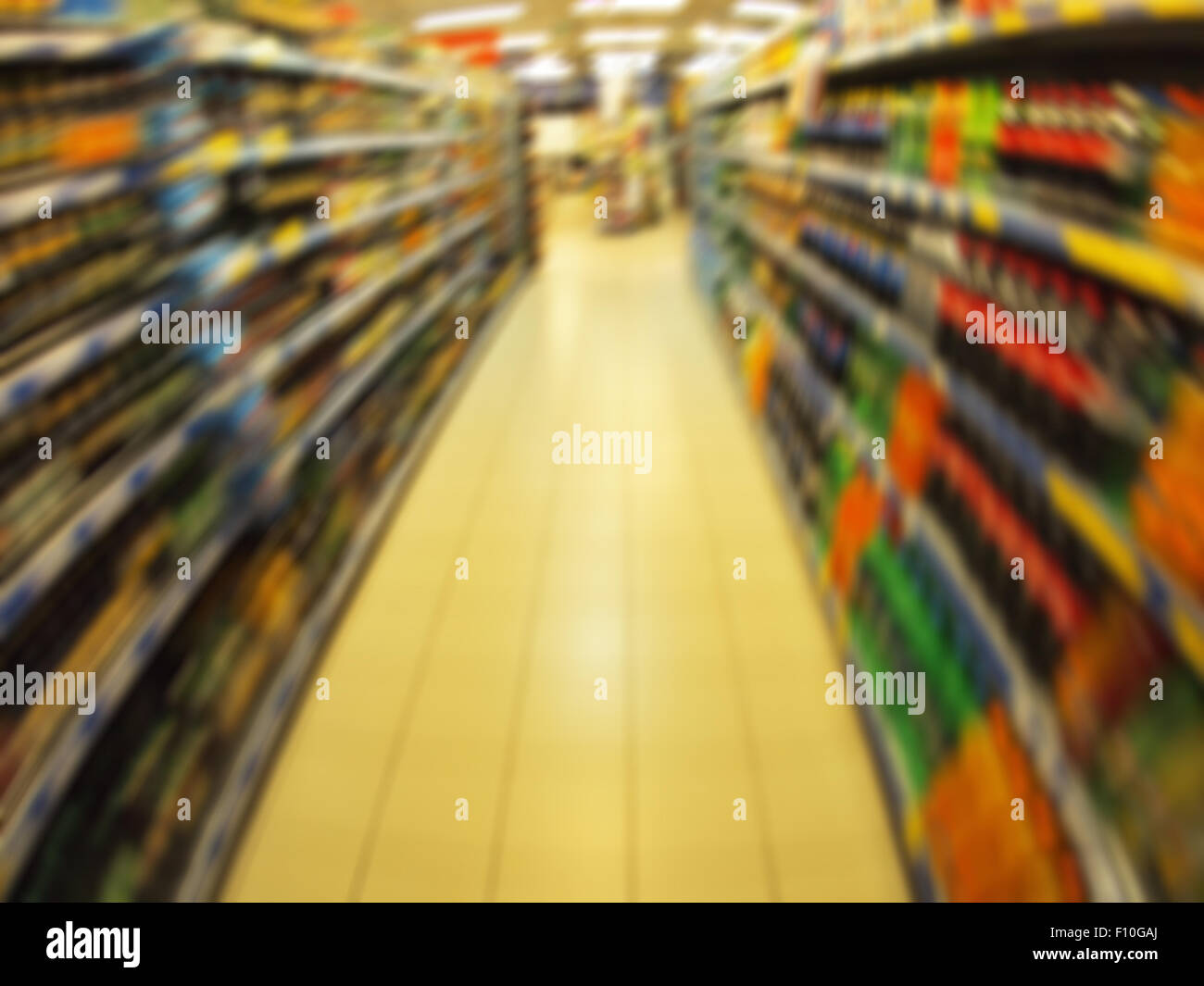 Defocused long shelf with sodas and juices in a supermarket with motion blur - Stock Image