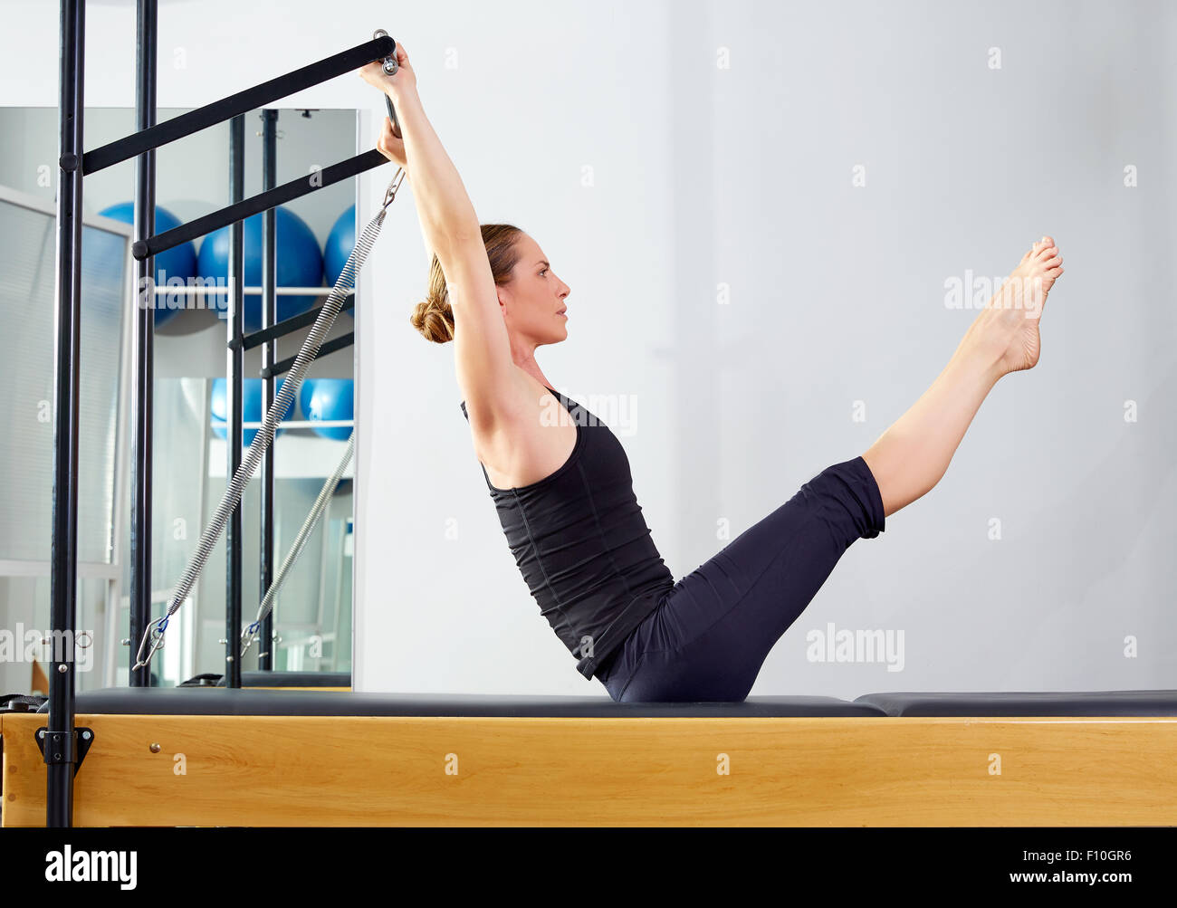 Pilates woman in reformer teaser exercise at gym indoor - Stock Image
