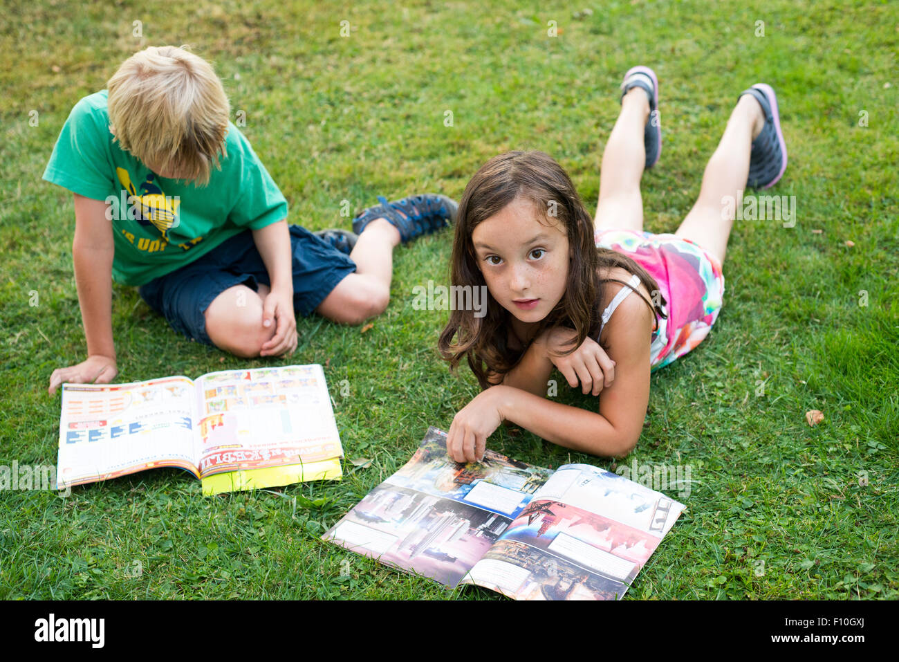 Kids reading together enjoying and reading a magazine laying on the grass outdoors Stock Photo