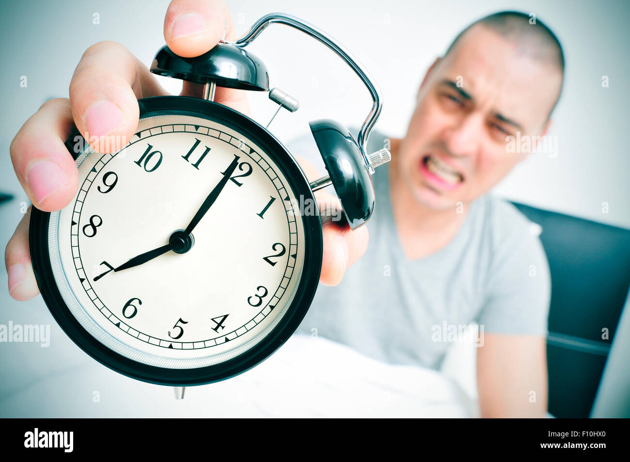 an angry young caucasian man in bed holds in his hand his alarm clock set at seven in the morning - Stock Image