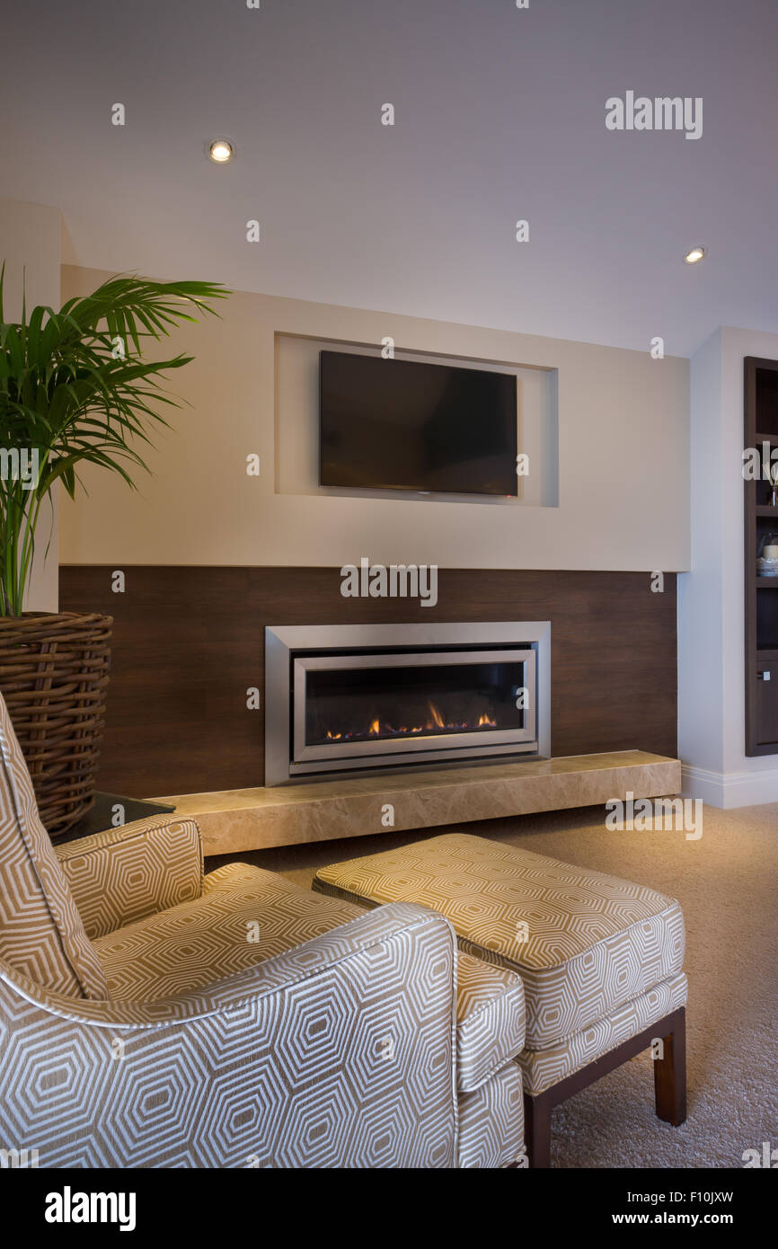 Comfy armchair placed in front of a modern glass fireplace and a tv set - Stock Image