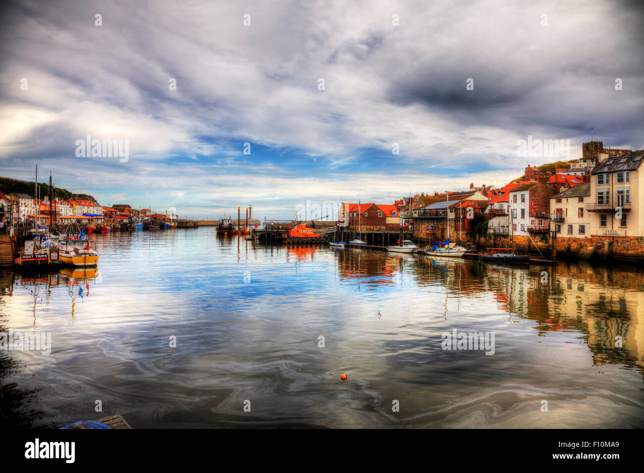 Whitby town harbour harbor coast coastal homes houses dramatic view scene sea pollution in water North Yorkshire - Stock Image