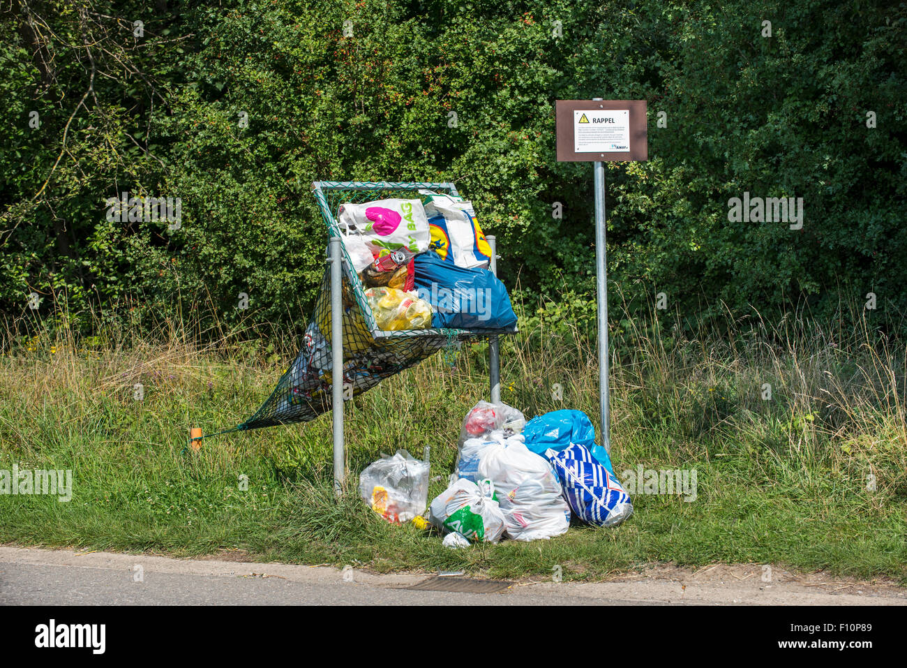 Illegal dumping of household refuse bags in net along roadside meant for throwing in cans and plastic bottles - Stock Image