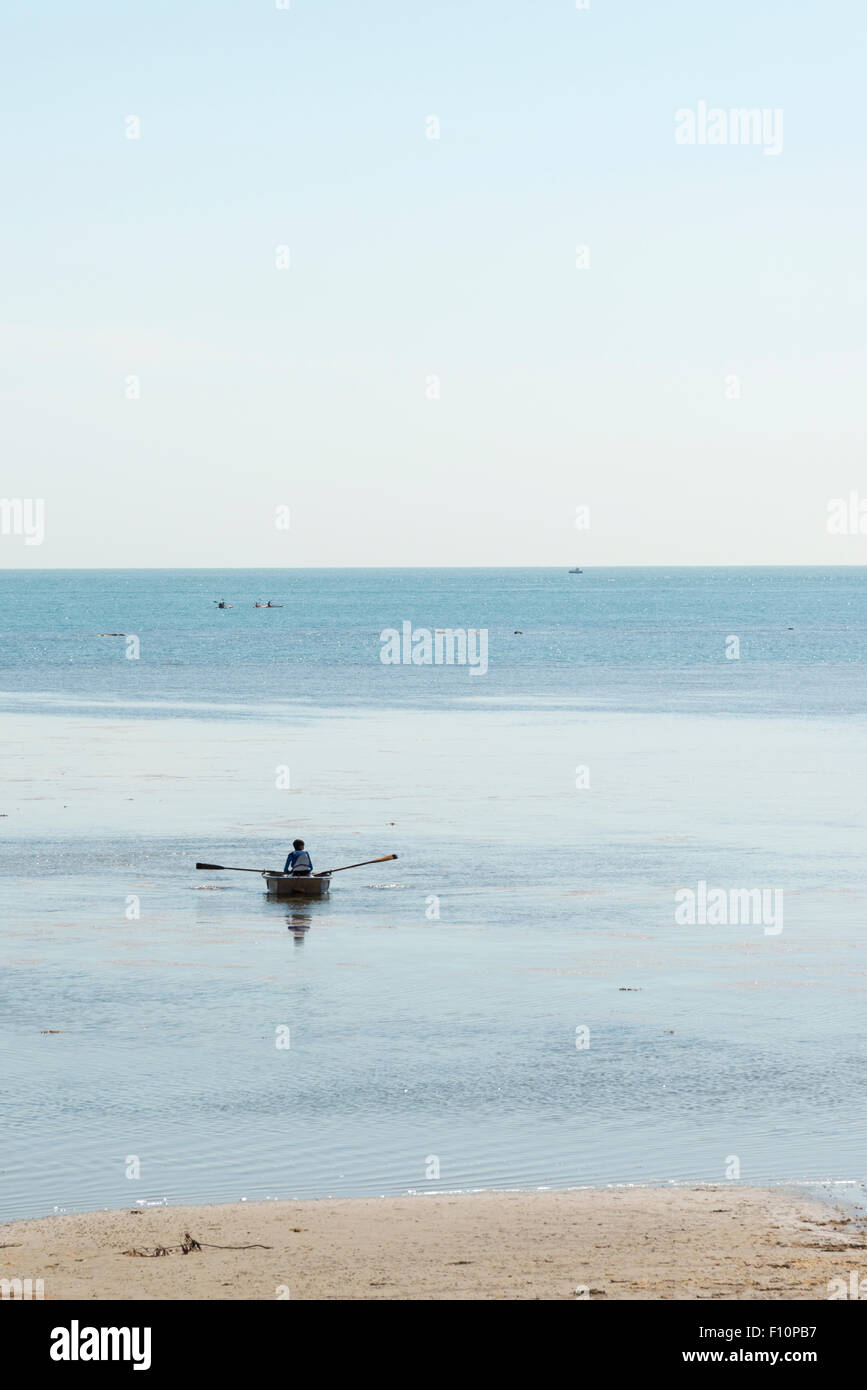 A person rowing a small boat on the sea shore at low tide at Bembridge Isle of Wight UK Stock Photo