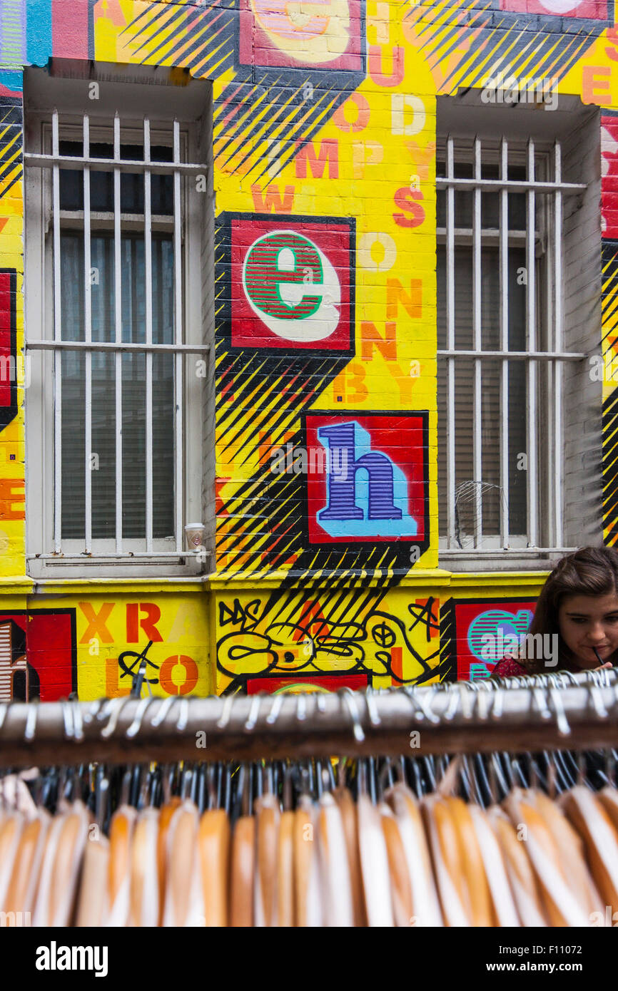 Girl shopping in front of a Ben Eine mural, Petticoat Lane market, London, England, United Kingdom - Stock Image
