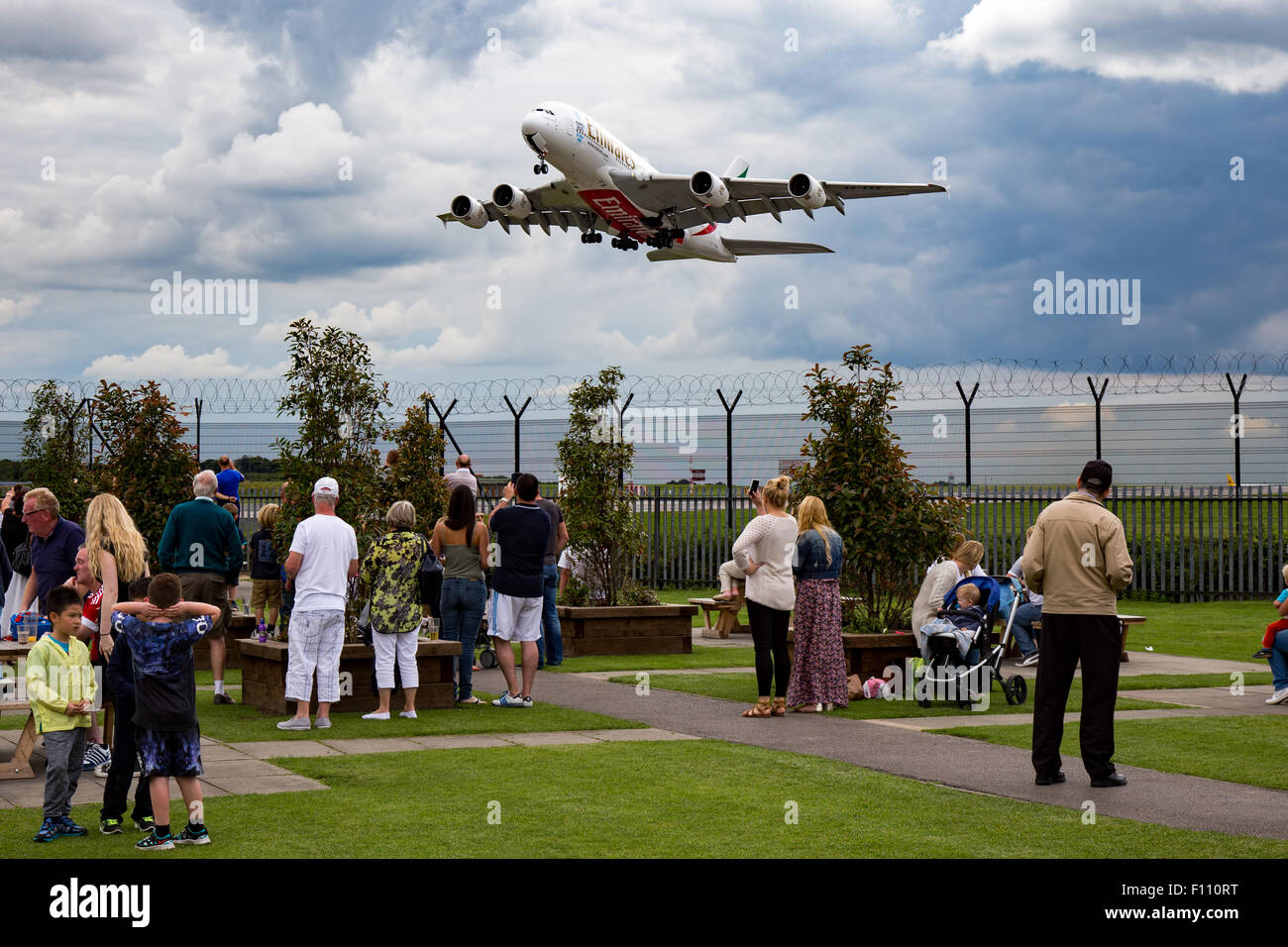 Emirates Airbus A380-800 climbs away from runway 05L at Manchester airport, as spectators watch on from 'The - Stock Image