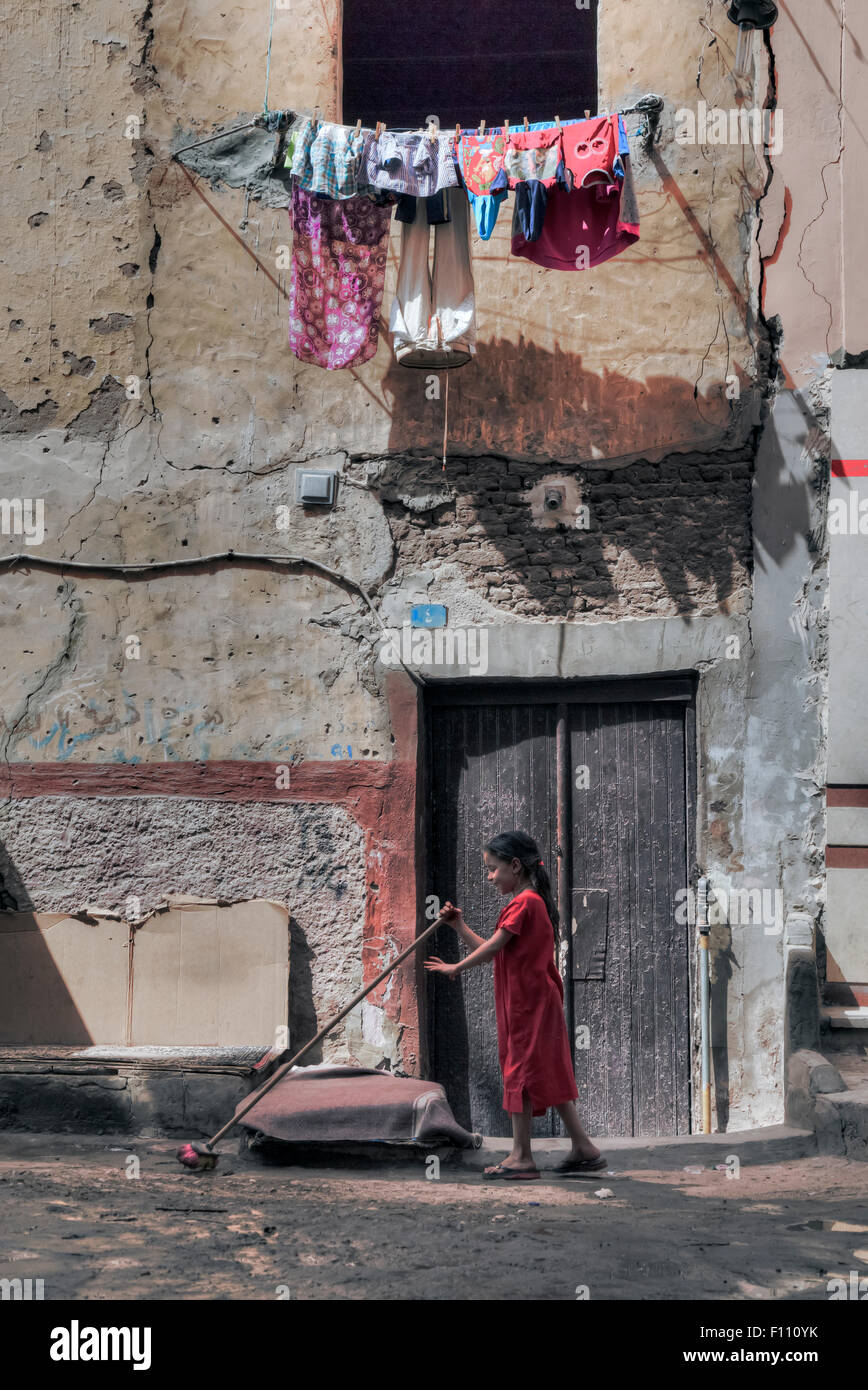 young girl sweeping the ground in the old Arabic city of Aswan, Egypt, Africa Stock Photo