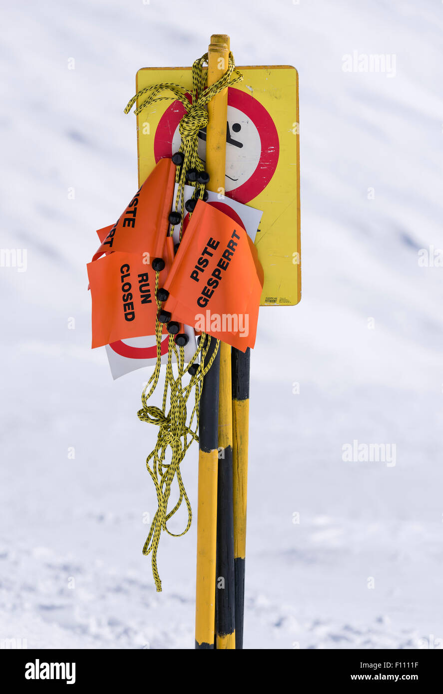 'Ski run closed' sign and barrier tape on a ski piste in the Swiss alps (Blatten/Belalp, canton Valais). - Stock Image